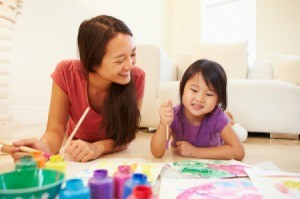 Babysitter and girl Lying On Floor And Painting Picture