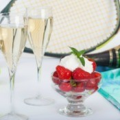 Table with tennis racket and balls, strawberries and champagne.