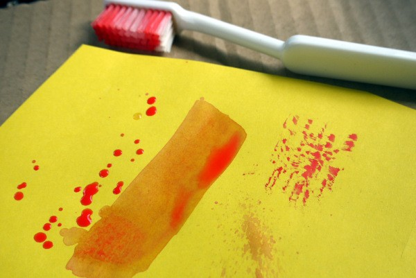 Use Old Toothbrushes in Your Craft Box - toothbrush and paint smear and spatters on yellow paper