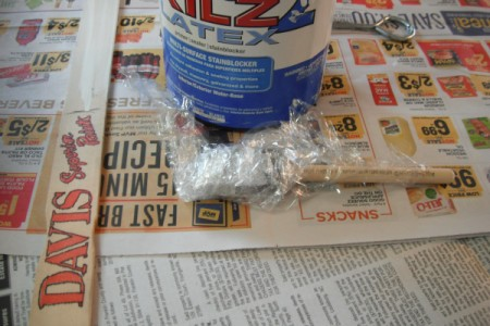 A paintbrush that is wrapped in plastic cling wrap.