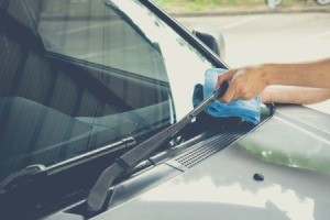 A person cleaning a windshield with a blue cloth.
