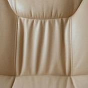 Back of a tan colored faux leather chair.