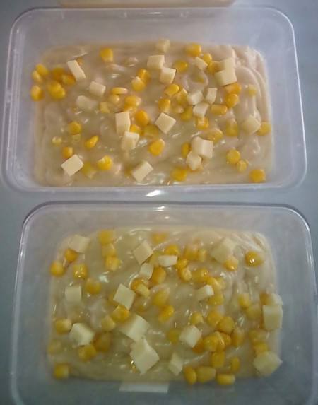 pudding in small containers with corn and cheese on top