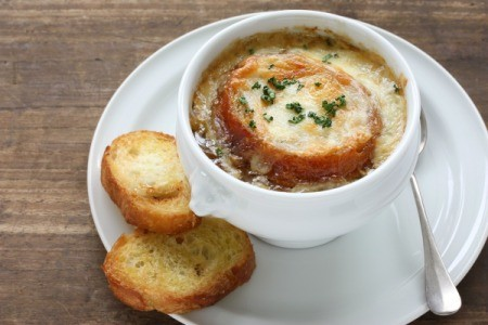 A bowl of French Onion soup with melted cheese over bread.