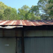 Inexpensive Roof Replacement for Low Income Homeowner - rusted tin roof on old mobile home