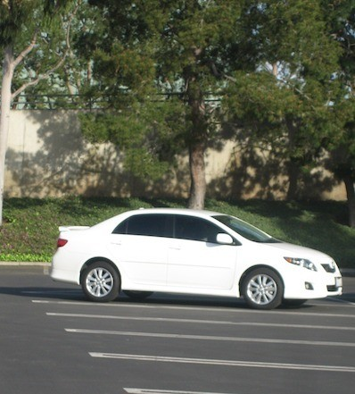 A white car parked in a parking lot.