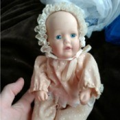 A porcelain baby doll by Dynasty Dolls