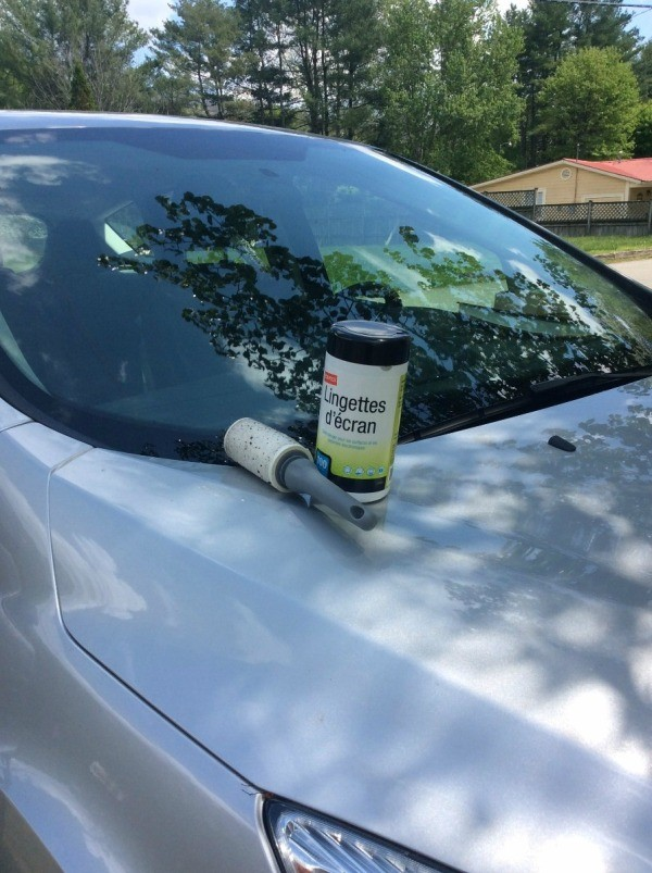 A clean car with a lint roller and cleaning wipes on the hood.