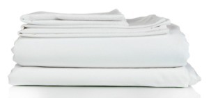 A set of white bedsheets, folded.