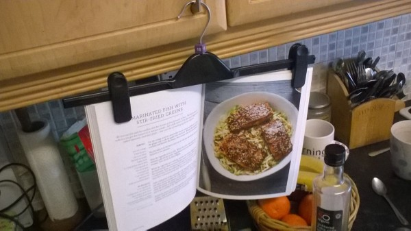 A pants hanger being used to display a cookbook in the kitchen.