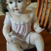 Information on Bisque Doll - ceramic baby doll wearing a pink dress