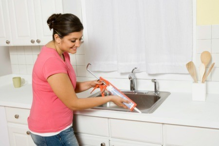 A woman caulking around a kitchen sink.