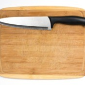 A bamboo cutting board with a sharp knife.
