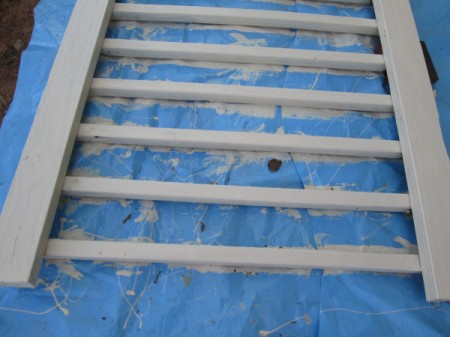Old Deck Railing Used For Garden Tool Storage - painted railing on blue tarp