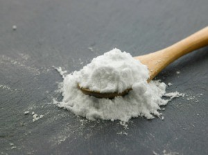 A white powder on a spoon, either baking soda or baking powder.