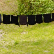 A row of black clothing on a clothesline.