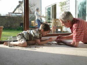 A man and his grandchild, counting change on the floor.