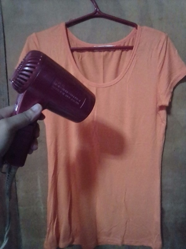 A hair dryer being used to remove wrinkles from a shirt.