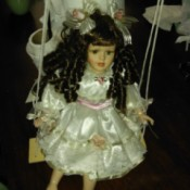 Value of Porcelain Doll and Figurine - doll on swing