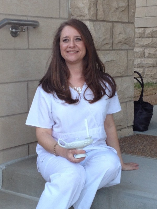 A woman wearing white nursing scrubs and a charm bracelet at her graduation from nursing school.