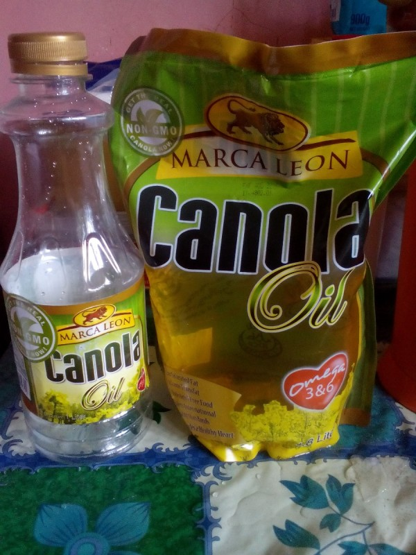 A bottle of canola oil next to a refill pack.
