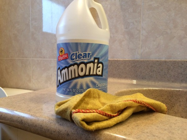 A bottle of ammonia and a cleaning rag in the bathroom.