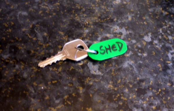 "A key with a green plastic fob that says ""SHED""."