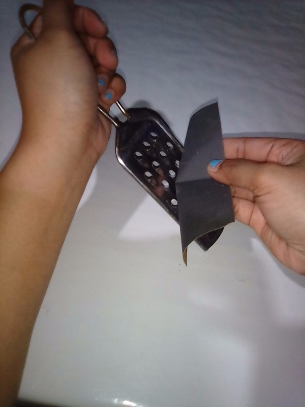 Rubbing sandpaper across a metal food grater.