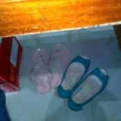 Two pairs of shoes under a worktable.