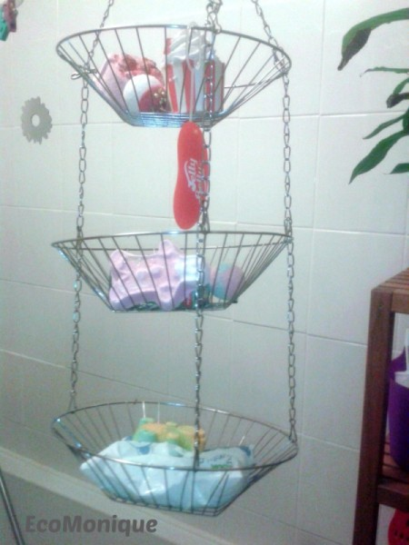 Shower supplies stored in a hanging wire fruit basket.