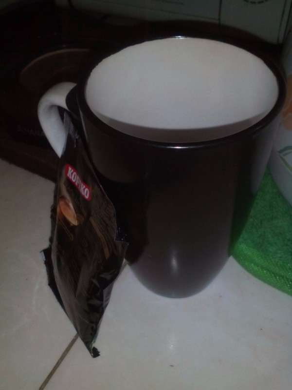 An empty mug next to a sachet of instant coffee.
