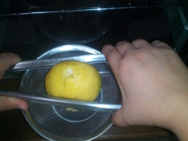 Using a pair of tongs to squeeze juice from a lemon.