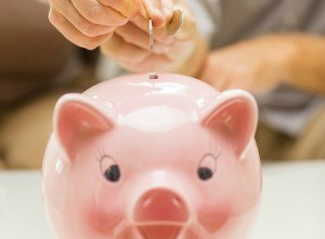 Two hands putting money into a piggy bank.
