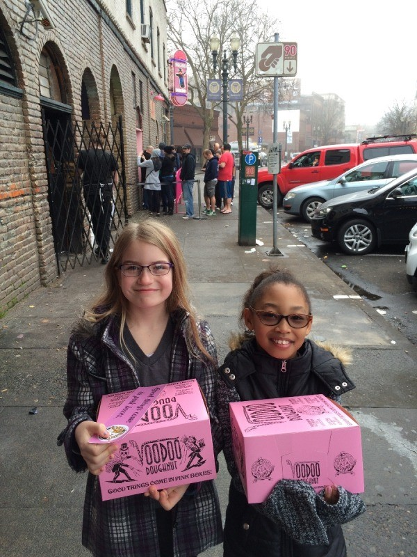 Visting Voodoo Doughnuts (Portland, OR) - girls carrying distinctive pink boxes of donuts