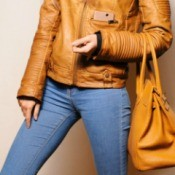 A woman wearing jeans carrying a leather purse.