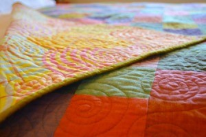 A colorful handmade quilt on a bed.