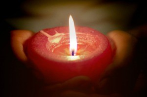 A person holding a red candle.
