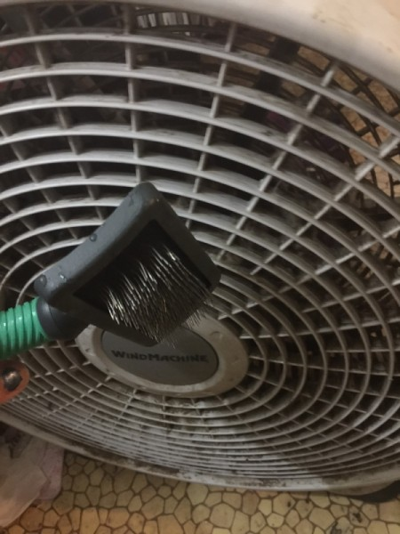 Cleaning a fan with a wire dog brush.