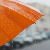 An orange umbrella in the rain.