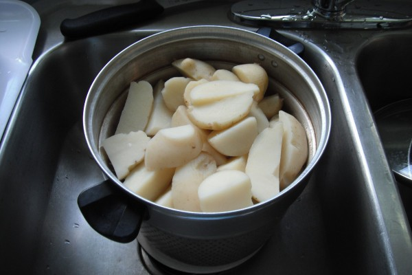 A pan full of cut and peeled red potatoes.
