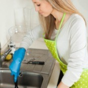 A woman using a plunger in a sink with a garbage disposal that won't drain.