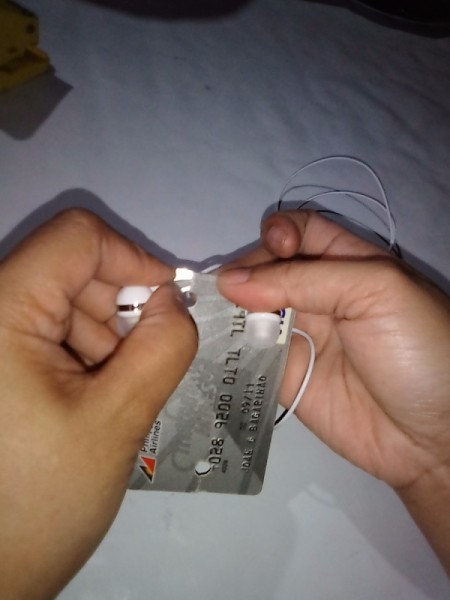 Expired Credit Cards for Storing Earphones - insert wire for earphones in the two top slits