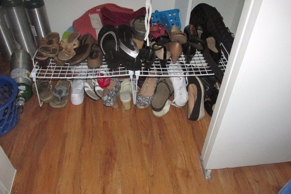 Shoes organized on a rack on the floor of a closet.