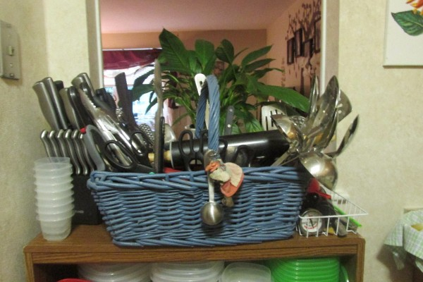 A basket for organizing flatware and kitchen tools.
