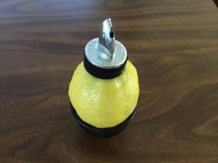 Using a oil bottle dispenser to juice a lemon.