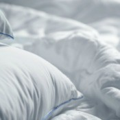 A white bed spread with white pillows