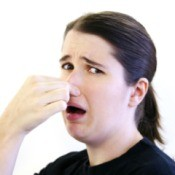 A woman holding her nose due to a rotten smell.