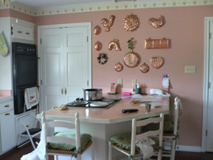 I have white cabinets with peach hardware, peach wallpaper, white trim, peach laminate countertops and dark brick color linoleum floor tile.