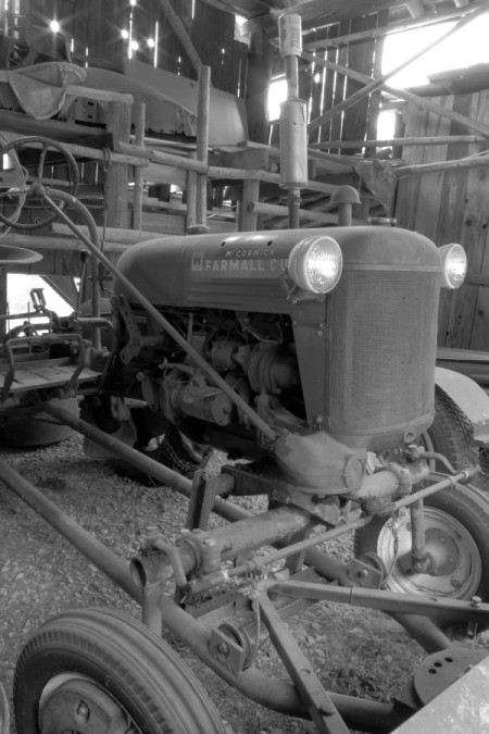 An old tractor in a wooden barn, in black and white
