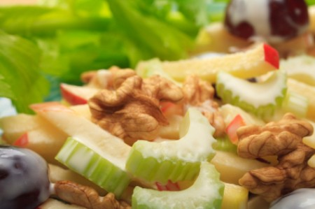 A close up of a salad with celery, grapes and apple